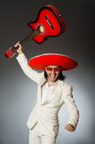 The funny mexican in suit holding guitar against Stock Photo
