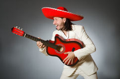 The funny mexican in suit holding guitar against Royalty Free Stock Photos