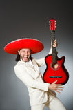 The funny mexican in suit holding guitar against Stock Image