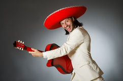 The funny mexican in suit holding guitar against Royalty Free Stock Photo