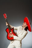 The funny mexican in suit holding guitar against Royalty Free Stock Images