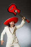 Funny mexican in suit holding guitar against gray Royalty Free Stock Photos