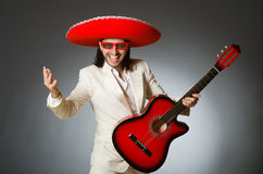 Funny mexican in suit holding guitar against gray Stock Image