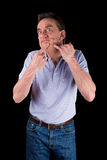 Funny Middle Age Man Squeezing Face. Black Background royalty free stock photography