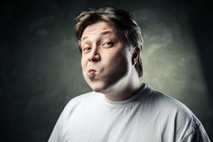 Funny middle aged acting ape man over gray Stock Photo