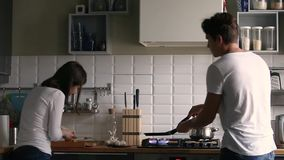 Funny millennial couple dancing while cooking together in the kitchen. Funny couple rear view dancing while cooking together in kitchen, young active family stock video