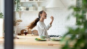 Happy girl have fun dancing cooking at home
