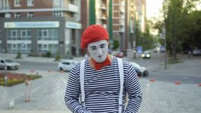 Funny mime invite handsome man to him. Funy mime in red beret and stripped shirt is posing for camera at fountains background. Street artist gesticulating hands stock video