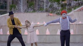 Funny mime and magician fighting for the girl. Illusionist and mime are showing performance at the urban street near fountains with illumination. Two artists stock video footage
