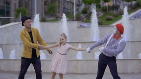Funny mime and magician pulling girl to himself by the hands. Illusionist and mime are showing performance at the urban street near fountains with illumination stock video footage