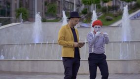Funny mime showing magician his professional skills with playing cards. Ilusionist and mime have fun standing near the illuminated fountains at the urban street stock video