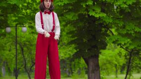 Funny mime walks on stilts and juggling in the park. Comical mime in wide red pants with suspenders, hat and a white shirt is juggling in the park. Performance stock video