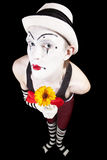 Funny mime in white hat with a bouquet of flowers Stock Photography