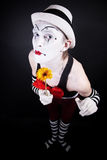 Funny mime in white hat with a bouquet of flowers Stock Photo