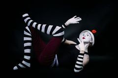Funny mime in white hat  lying on floor Royalty Free Stock Images