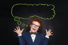 Funny mischievous child boy and empty speech clouds bubbles on chalkboard background.  stock photo