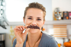 Funny modern housewife making mustache with Halloween biscuit Royalty Free Stock Image