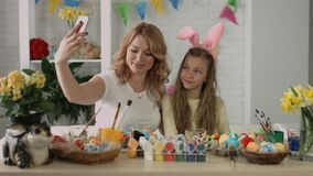 Funny mom and daughter making holiday selfie on the phone. Easter stock footage