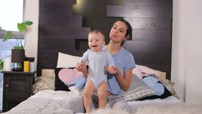 A young mother and her little one-year-old son are jump at home on the bed. Funny mom and her little one-year-old son have fun in the morning in bed, they dance stock video footage