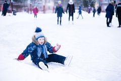 Funny moment - cute little boy fell on the ice skating rink.  royalty free stock image