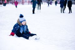 Funny moment - cute little boy fell on the ice skating rink.  stock photos