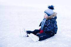 Funny moment - cute little boy fell on the ice skating rink.  stock images