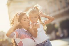 Funny moment for us. Mother and daughter taking self portrait on city street. Copy space stock photos