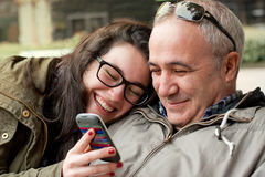 Funny moments with dad. Father and teenager daughter with head in his shoulder sharing something funny in a mobile phone Stock Photos