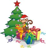 Funny monkey with gift boxes near the Christmas tree Royalty Free Stock Images