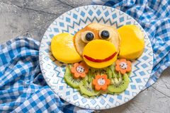 Funny monkey pancakes for kids breakfast. Funny monkey pancakes with fruits for kids breakfast Royalty Free Stock Photo