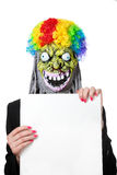 Funny monster with white blank banner. Funny monster in clown's wig with white blank banner isolated on white background stock photo