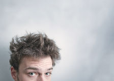 I need a hair cut !. Funny morning look of a young adult man with on a white (greenish/blueish) background - not isolated. This is also the Hangover or just a Royalty Free Stock Image