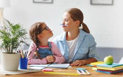 Funny mother and child daughter doing homework writing and readi stock photography