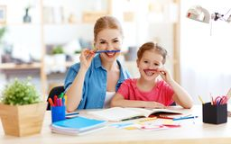 Funny mother and child daughter doing homework writing and reading. At home royalty free stock photo