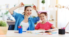 Funny mother and child daughter doing homework writing and reading. At home stock photo