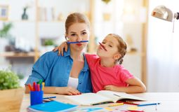 Funny mother and child daughter doing homework writing and reading. At home stock images