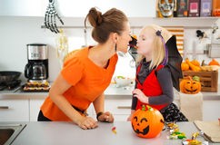 Funny mother with daughter in bat costume eating halloween candy Stock Photo