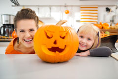 Funny mother with daughter in Halloween decorated kitchen. Funny modern mother with daughter in bat costume looking out from big orange pumpkin Jack-O-Lantern in Royalty Free Stock Images