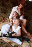 Funny mother and daughter. Young mother with two daughters sitting on hay ranch in the American stock photo
