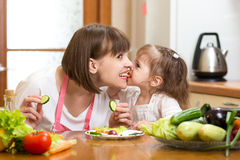 Funny mother and kid eating vegetables in kitchen Stock Image