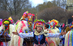 Funny motley mummers. Funny man giving away kisses dressed in traditional old female clothes part of mummer group in ornate costumes at Varna Carnival parade on Royalty Free Stock Photo