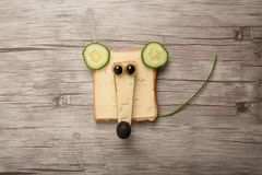Funny mouse made of bread and cheese. On wooden background Royalty Free Stock Photo