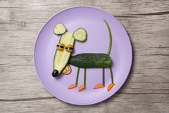 Funny mouse made of cucumber on plate and board. Mouse made with cucumber, carrot, onion, corn, radish, olive. Shot with Canon 5D, ISO 100 on wooden background Stock Photography