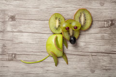 Funny mouse made of green fruits. On wood Royalty Free Stock Photos