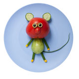 Funny mouse made of red and green tomato. On plate Royalty Free Stock Photo