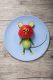 Funny mouse made of red and green tomato. On plate and desk Royalty Free Stock Photography