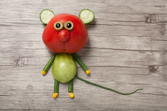 Funny mouse made of red and green tomato. On wooden background Stock Photography