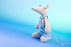 Funny mouse toy climbing. Funny mouse toy walking up on blue background Royalty Free Stock Photography