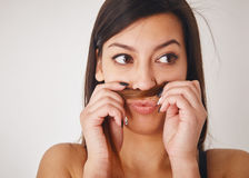 Funny Moustache. Close up funny young woman putting her hair between nose and lip and looking away Royalty Free Stock Image