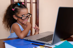 Funny multiracial small girl wearing glasses and using a laptop Royalty Free Stock Photo